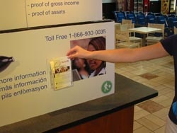 A hand grabs a Coordinated Care brochure from a display
