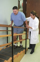 A man performing a rehabilitation exercise walking up steps while a Healey therapist assists him