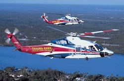 Two Trauma Hawk helicopters flying side by side over water.