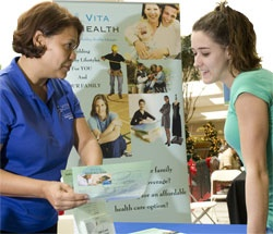 Health Care District employee explains the Vita Health program to an interested woman
