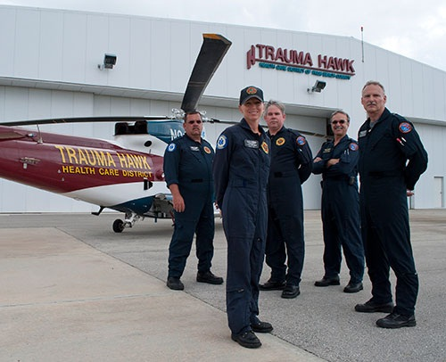 Flight crew standing in front of a Trauma Hawk helicopter