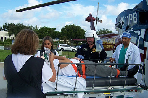 A patient on a gurney unloaded from the Trauma Hawk receiving medical care
