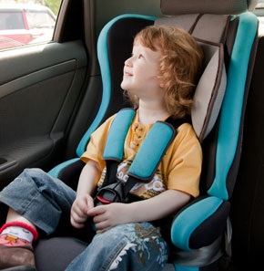 A child sitting in a safety seat in a car