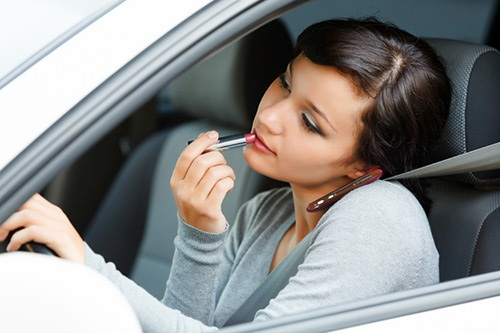 A young woman applying makeup in the car while driving