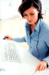 A woman wearing a headset sits in front of a computer