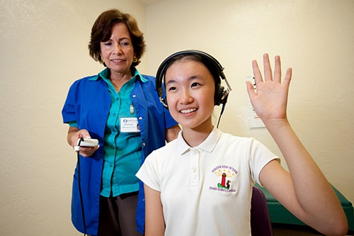 A student raises her hand signaling she can hear the beep during a hearing test a tech is performing