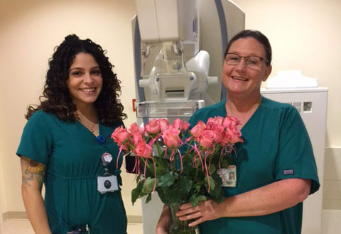 Melissa and Michelle. Michelle is holding a bouquet of pink flowers.