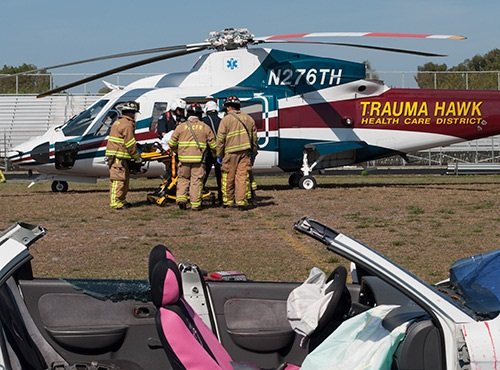 A mock patient being loaded into a Trauma Hawk helicopter