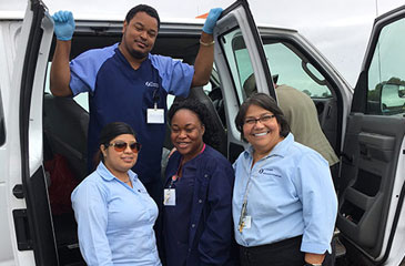 Four Brumback Clinic staff stand by the side of a white van with open doors