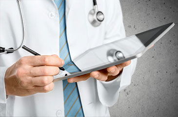 Close of a doctors hands holding a tablet and using a stylus