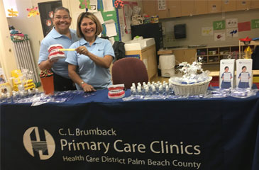 Millie and Gladys pose for a picture behind the Brumback Clinics table at the Dental Fair Expo.