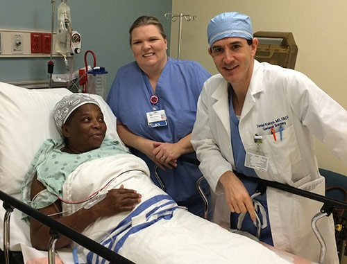 Doctor Daniel Kairys and nurse Pam Ellison stand next to a patient in bed