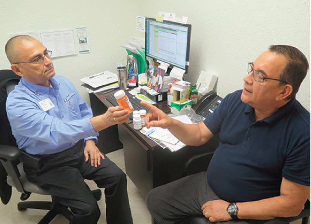 Marco holding a bottle of pills explains a medication to a patient