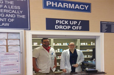 Nicholas Netzer and Jennifer Dively stand at the pharmacy pick up and drop off window
