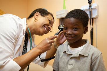 Doctor performs an ear examination on a child.