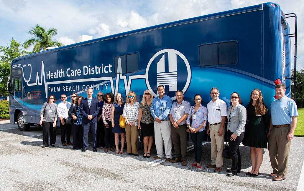 H C D Staff standing in front of new mobile medical unit