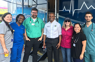 District staff in front of the mobile health clinic