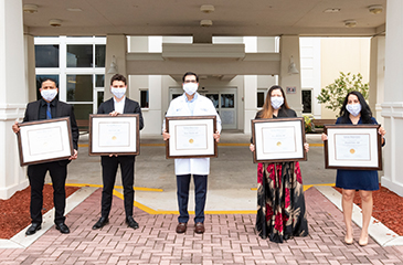 Image of the 5 graduates in front of the hospital